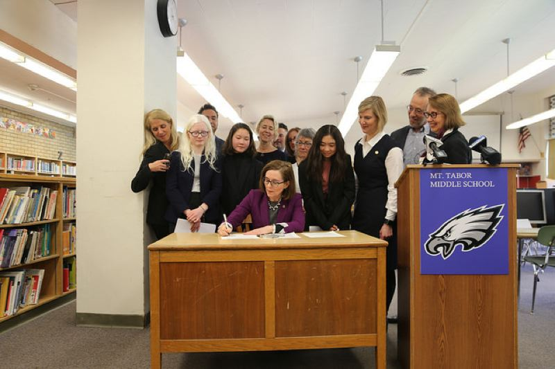 COURTESY PHOTO - Gov. Kate Brown signs House Bill 4155 at Mt. Tabor Middle School Monday, April 9, 2018. The bill requires public bodies to buy internet services only from companies that practice 'net neutrality,' the practice of not charging different rates, blocking or slowing down certain websites.