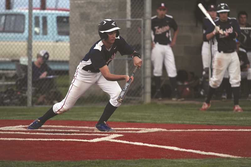PHIL HAWKINS -  Kennedy senior Jonathan Valladares drops down a bunt in the No. 2 Trojans' 17-1 victory over the East Linn Christian Eagles on Friday.