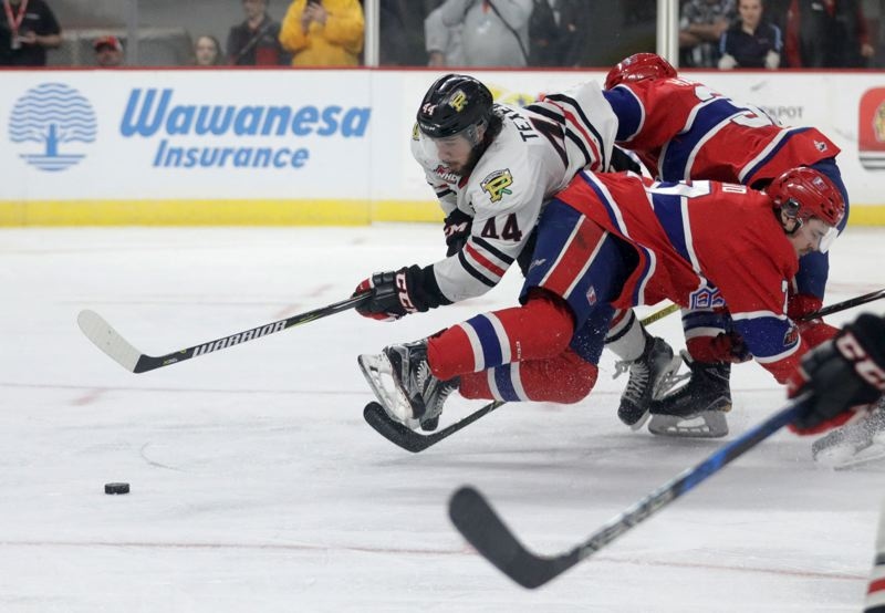 TRIBUNE PHOTO: JONATHAN HOUSE - Keoni Texeira, Portland Winterhawks captain and defenseman, tries to get through a double-team of Spokane Chiefs during a first-round game in the Western Hockey League playoffs.