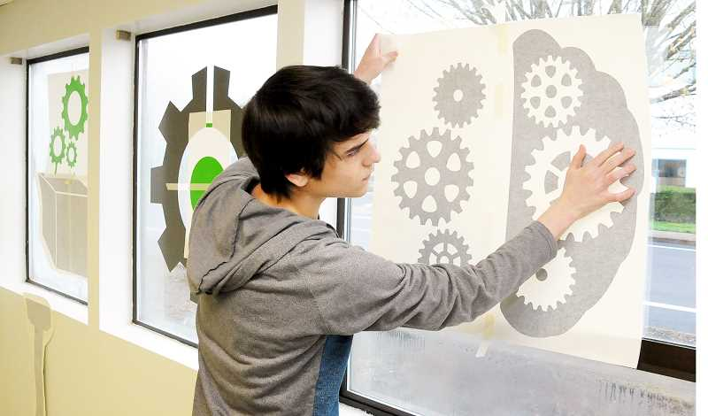 GARY ALLEN - Newberg High School sophomore Ryan Harber applies a graphic decoration to the Cache Room at the Chehalem Valley Innovation Accelerator last month. Harber won a contest in teacher Tyson Lunden's class to design the decorations for the room, which were then manufactured by Newberg-based Phat GFX.