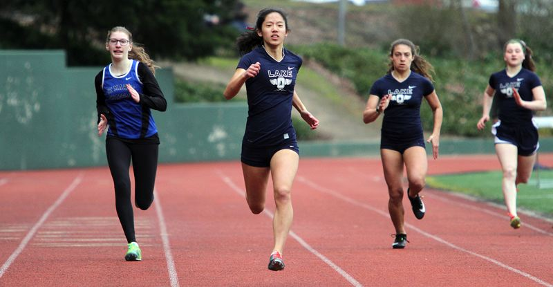 REVIEW PHOTO: MILES VANCE - Lake Oswego junior Erica Chiang (center) sprints home to win the 400 meters against both St. Mary's and West Linn last week at West Linn High School.
