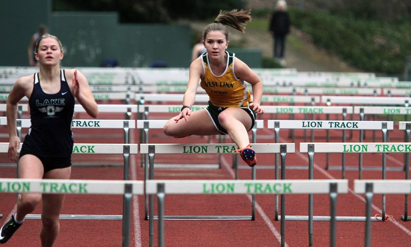 TIDINGS PHOTO: MILES VANCE - West Linn junior Sophie Conrad clears a hurdle during her team's meet against both St. Marys and Lake Oswego last week at West Linn High School.