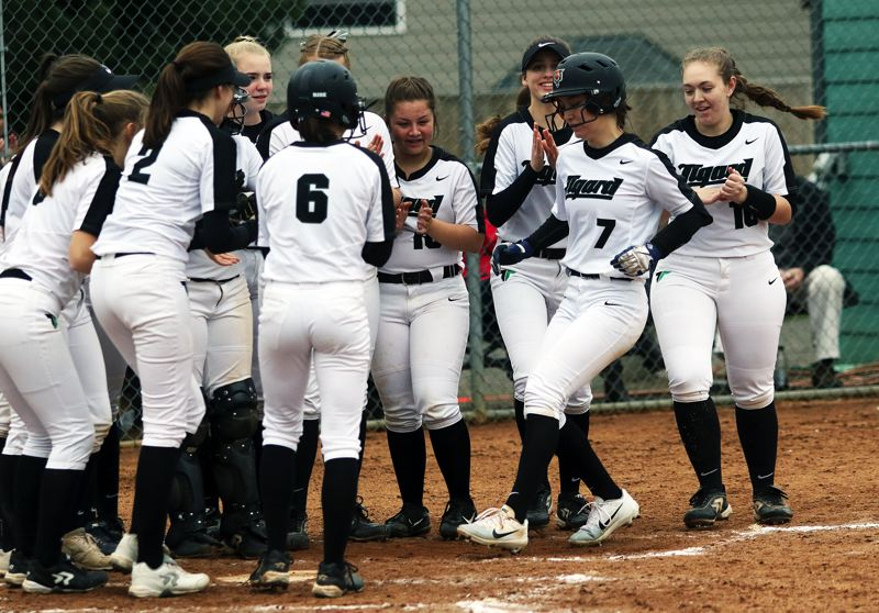 TIMES PHOTO: DAN BROOD  - The Tigard High School softball team greets sophomore Lexi Klum at home plate following her home run against Reynolds.
