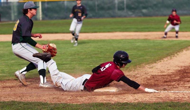 TIMES PHOTO: DAN BROOD - Tualatin High School senior Colby Jackson dives safely to first base for a two-run infield single during Mondays game with West Linn.