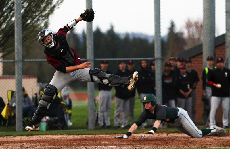 TIMES PHOTO: DAN BROOD - Tualatin High School senior catcher Cole Kinman (left) leaps for the ball as West Linns J.J. Hoover dives to home plate during Mondays game.