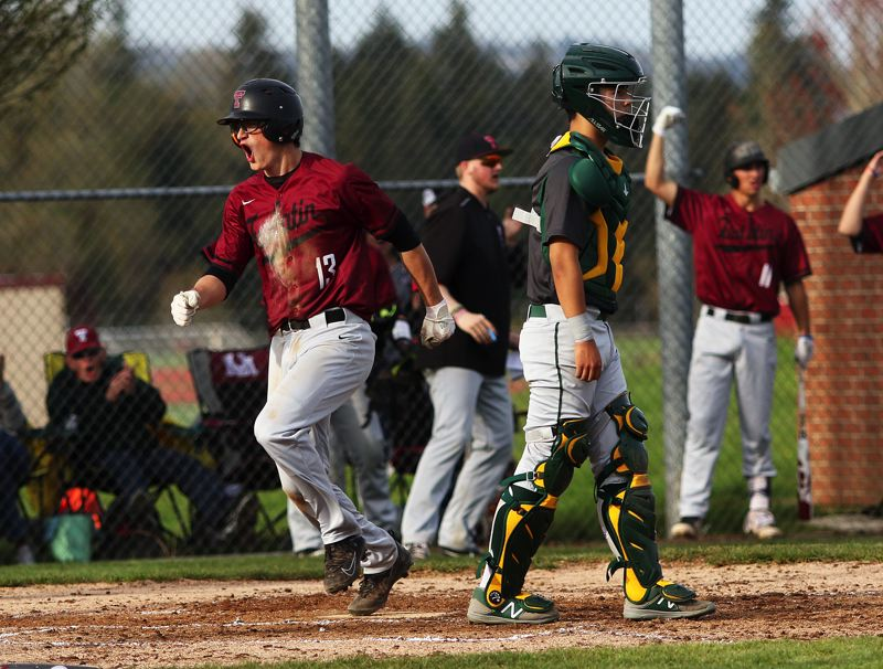 TIMES PHOTO: DAN BROOD - Tualatin High School senior Colby Jackson (13) lets out a yell as he crosses home plate in the second inning of Mondays game with West Linn.