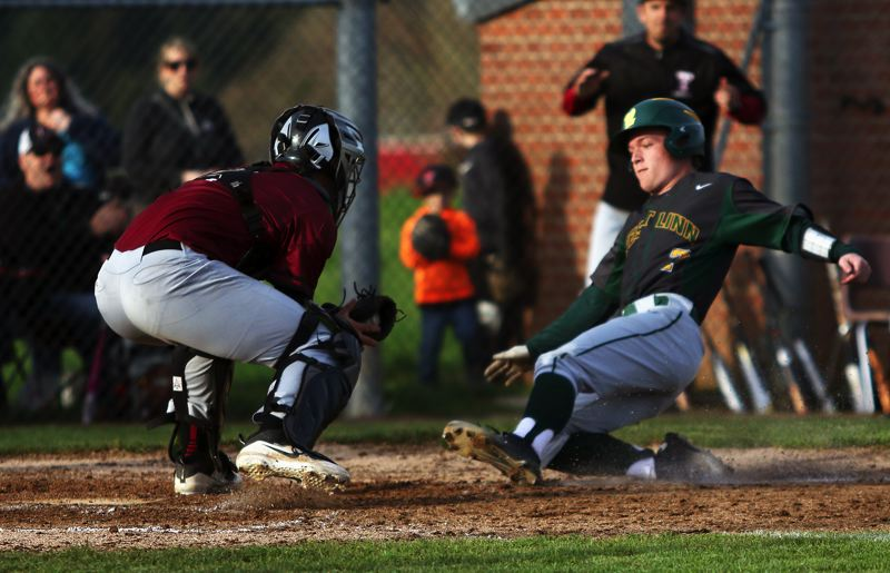 TIMES PHOTO: DAN BROOD - Tualatin senior catcher Cole Kinman (left) gets ready to tag out West Linn junior Alex Nicolaes at the plate.