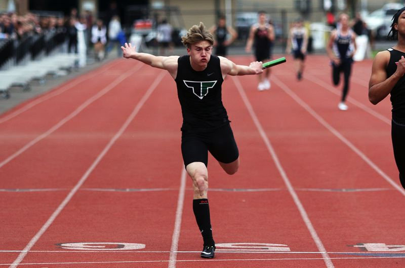 TIMES PHOTO: DAN BROOD - Tigard High School senior Skylar Holloway leans at the finish line during the 4 x 100-meter relay event at last weeks meet.