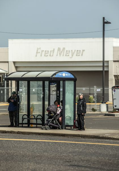 TRIBUNE PHOTO: JONATHAN HOUSE - TriMet riders wait for the bus in front of the now-closed Fred Meyer on 82nd Ave.