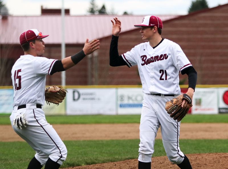 DAN BROOD - Sherwood junior relief pitcher Braden Thorn (21) celebrates with senior Jacob Matzat following the final out of the Bowmen's 5-4 home win over Tigard.