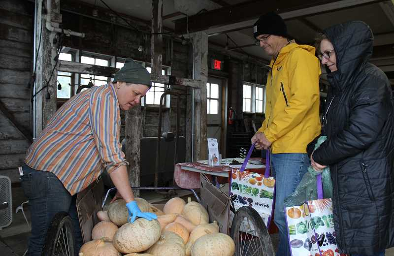 REVIEW PHOTO: SAM STITES - Trish Hall (left) of 47th Avenue Farm helps a pair of CSA customers pick out a winter squash.