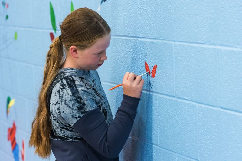 STAFF PHOTO: CHRISTOPHER OERTELL - Leadership student, Cali Davis, 10, paints a butterfly on the mural at Harvey Clarke Elementary.