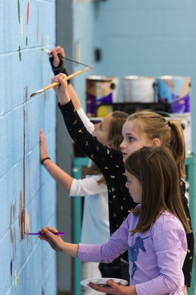 STAFF PHOTO: CHRISTOPHER OERTELL - Timmery Waldron, 7, and Madelyn Frost, 8, work on the gym's mural before school.