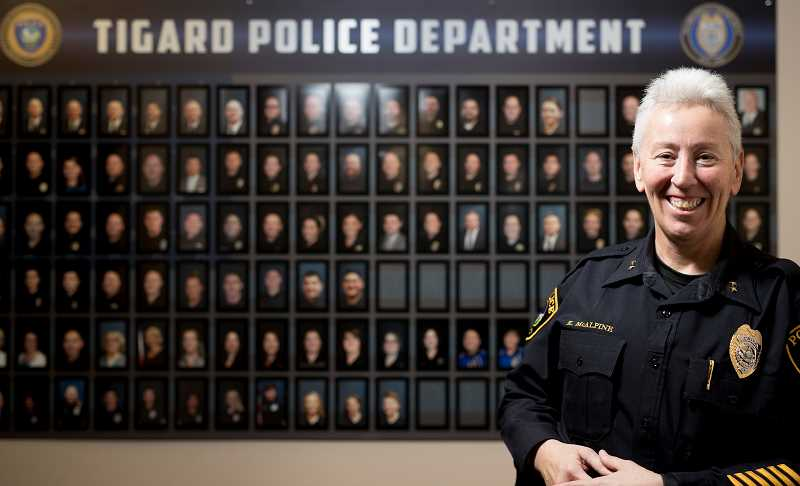 TIMES PHOTO: JAIME VALDEZ - Tigard Police Chief Kathy McAlpine, standing in front of photos of officers and staff, reflects on her first year as chief. McAlpine oversees a department of 60 officers.