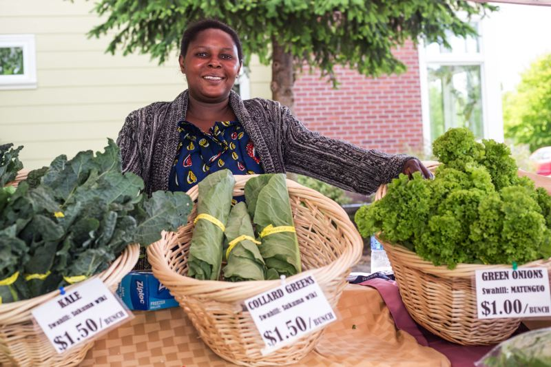 STAFF PHOTO: JONATHAN HOUSE - Rosata Niyonzima sells produce at the Village Gardens Farmers Market in North Portland. Gaston is getting its own farmers' market this year. It opens May 17 and will run into October.