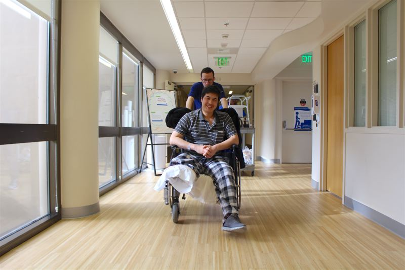 REVIEW PHOTO: SAM STITES - Mohammad Fawad Mohammadi smiles as he's wheeled out of Legacy Emanuel Medical Center on Thursday after more than a month in recovery from a brutal attack took his right leg.