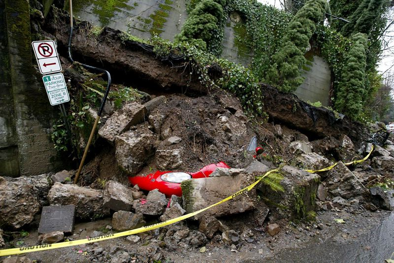 PAMPLIN MEDIA GROUP FILE PHOTO - A January 2006 landslide damaged property on Southwest Cardinell Street, crushing two cars beneath the rubble.