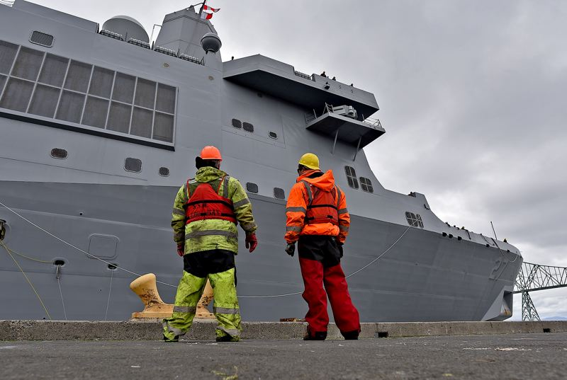 COURTESY PHOTO: COLIN MURPHEY/THE DAILY ASTORIAN - Dock workers watch as the USS Portland moors in Astoria Thursday, April 12, before beginning its trip down the Columbia River to Portland.