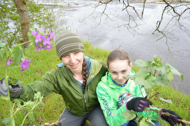MARK KIRCHMEIER, FOR THE SPOTLIGHT - Scappoose Bay Watershed Council manager Amber Kester and daughter, Kallee, 11, holding freshy dug up invasive lunaria.
