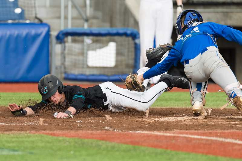 STAFF PHOTO: CHRISTOPHER OERTELL - Century's Keaton Johnson slides head first into home plate during the Jaguars' game against McNary April 12 at Ron Tonkin Field.