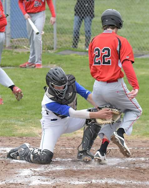 LON AUSTIN/CENTRAL OREGONIAN - Corbett's Cameron Johnsen beats a tag at the plate in the Cardinals' three-run third inning in the first game a doubleheader. Despite the runs, the Cardinals lost 9-3 and 11-1 to the Crook County Cowboys.