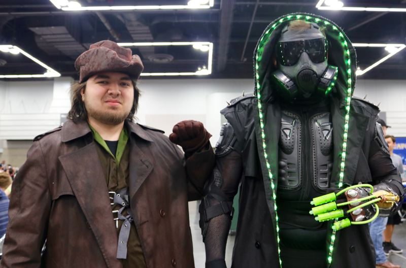 TRIBUNE PHOTO: ZANE SPARLING - FROM LEFT: Antonio Cordero and Brodie Marlatt, both residents of Grants Pass, pose for a photo on Saturday, April 14 at the Wizard World Comic Con in Portland. Cordero is dressed as a hunter from the video game 'Bloodborne,' while Marlatt is dressed as a character of his own design.