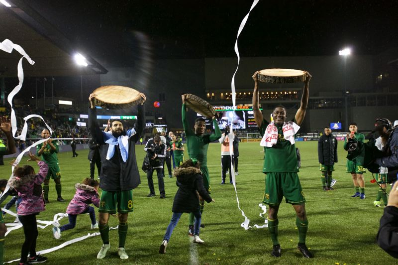 TRIBUNE PHOTO: JOSH KULLA - From left, Portland Timbers Diego Valeri, Alvas Powell and Fanendo Adi raise their wooden slabs after a 3-2 victory over Minnesota United at Providence Park on Saturday night.
