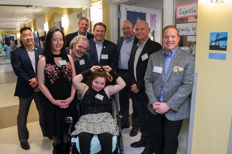 PROVIDENCE PORTLAND MEDICAL CENTER - The Providence Center for Medically Fragile Children resident Camille Stewart and her parents Christina and Bill Stewart (left) at her room in the center with (from left) Jason Hirata, Subaru of America, Ben Bradshaw, Carr Subaru, Jim Pernas, Subaru of America, Pete Holt, Subaru of America, Fernando Del Campo, Carr Subaru and Michael Parks, Carr Subaru. The room is dedicated to Carr Subaru and Subaru of America for their ongoing support of the Center for Medically Fragile Children.