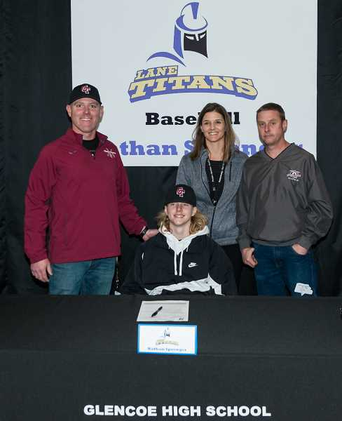 STAFF PHOTO: CHRISTOPHER OERTELL - Glencoe's Nathan Sprenger signs his letter of intent to play baseball at Lane Community College with his parents and Tide head coach Tim Stewart April 11 at Glencoe High.