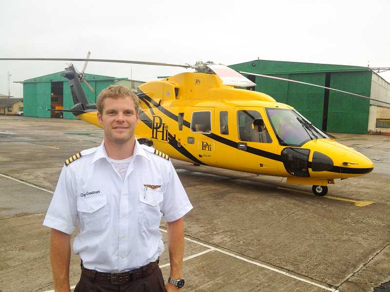 PHOTO SUBMITTED BY CLAY GOODMAN - Clay Goodman poses in front of a PHI helicopter in Takoradi, Ghana.