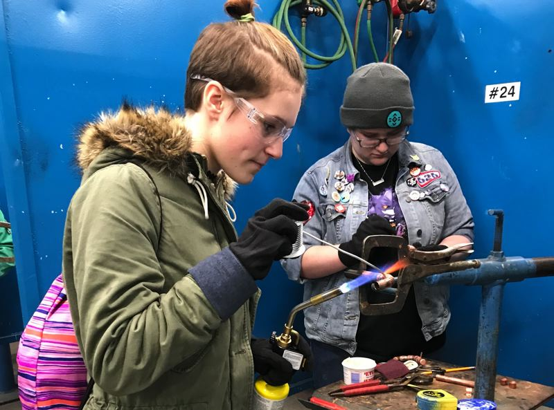 PHOTO COURTESY: MICHAEL CLARK - Jasper Stites and Ella Ferguson practice welding during a plumbing trades tour.