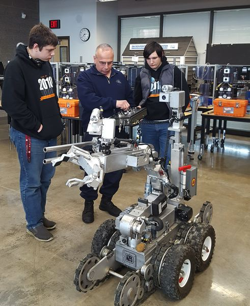 PHOTO COURTESY: LESLIE ROBINETTE - Gladstone High School seniors Billy Siegle and Josh Skinner ask questions about a bomb squad robot strong enough to lift a human body.