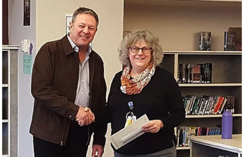 PHOTO COURTESY: NCEF - North Clackamas Education Foundation board member Gary Chapman presents a grant award to Claudia Carle of Alder Creek Middle School.