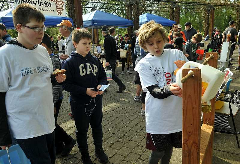 REVIEW PHOTO: VERN UYETAKE - Henry Pinetner demonstrates a tip-tap water dispenser used by villagers in Africa at one of the informational booths created by local students for last year's Walk4Water. Children from Lake Oswego's Oak Creek Elementary School will join the fun this year.