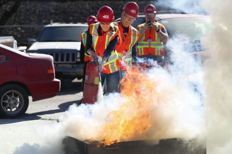 PORTLAND TRIBUNE: JESSIE DARLAND - NET trainees use the buddy system when learning to put out a gas fire. This was part of their final volunteer training on March 31 where they also practiced search and rescue exercises, triage, and learned how to shut off utilities in homes.