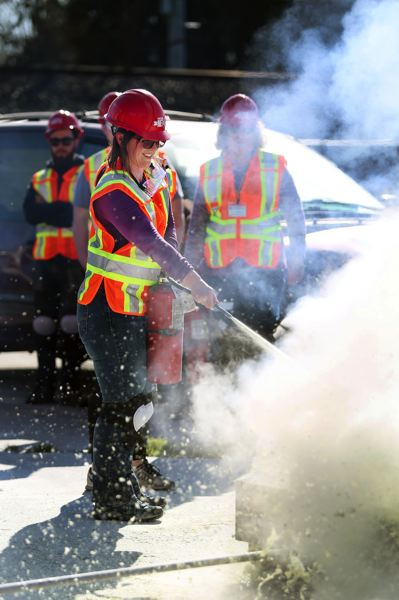 PORTLAND TRIBUNE: JESSIE DARLAND - Two NET trainees approach a chemical fire and practice using extinguishers. The trainees were shown how water doesn't work on chemical fires, and took turns using foam to put out the flames.