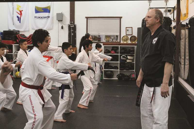 LINDSAY KEEFER - Ken Olcott (right) leads one of his taekwondo classes in warmups at Counter Point Martial Arts in Hubbard. Olcott recently returned from a trip to South Korea, where he received the rank of 8th Dan taekwondo grandmaster.