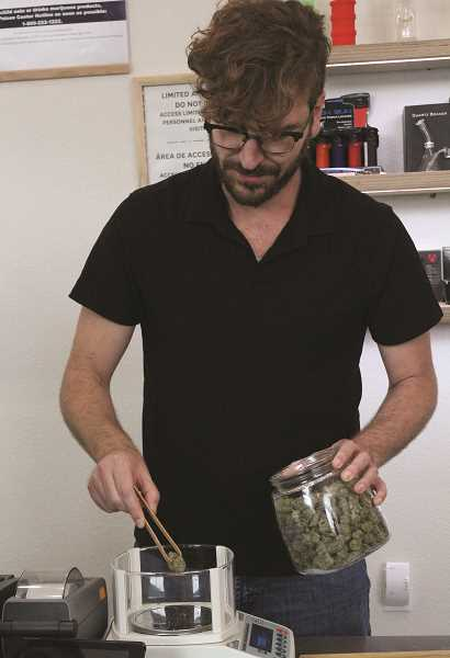 LINDSAY KEEFER - Budtender Francisco Montero measures out a customer's order at Treestar dispensary.