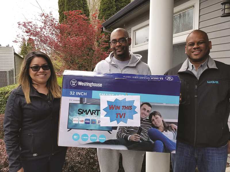 COURTESY PHOTO: TOM MCFADDEN - Wave Oregon retail manager Claudia Zepeda and direct sales Manager Malcolm Brooks flank prize winner Jamil Nested.