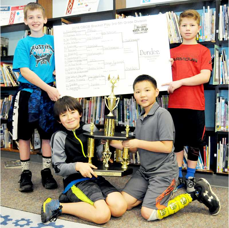 SETH GORDON - Clockwise from upper left: Donovan Milstead, Ben Clodfelter, Josef Moisan and Kota Yamamoto hold the state championship trophy and the championship bracket they earned for winning the 3rd-5th grade division at the Oregon Battle of the Books state meet at Chemeketa Community College April 7 in Salem.