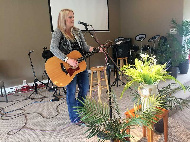 ESTACADA NEWS PHOTO: EMILY LINDSTRAND - Jessica Elliot smiles as she plays guitar at Estacada Community Fellowship. Elliot will release three new singles this year, following up to her debut album Jessie Leigh.