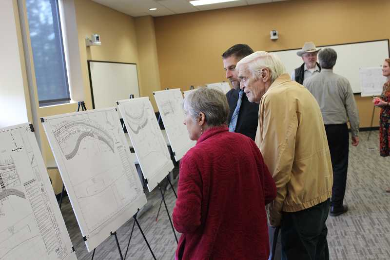SPOKESMAN PHOTO: COREY BUCHANAN - Wilsonville resident Tom Bernert (middle) looks at designs for the 5th Street to Kinsman Road extension project.