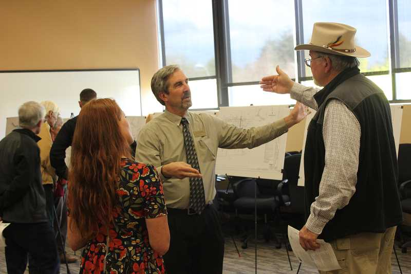 City of Wilsonville engineer Steve Adams (middle) talks with open house attendee John Holmes (right).