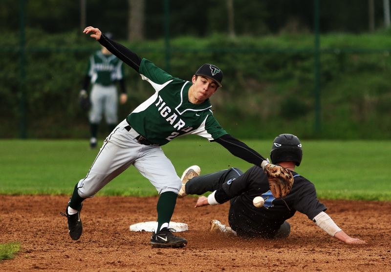 TIMES PHOTO: DAN BROOD - Tigard senior shortstop Michael Quintana (left) reaches for the ball as Lakeridge junior Casey Smith slides to second base during Tuesdays game.