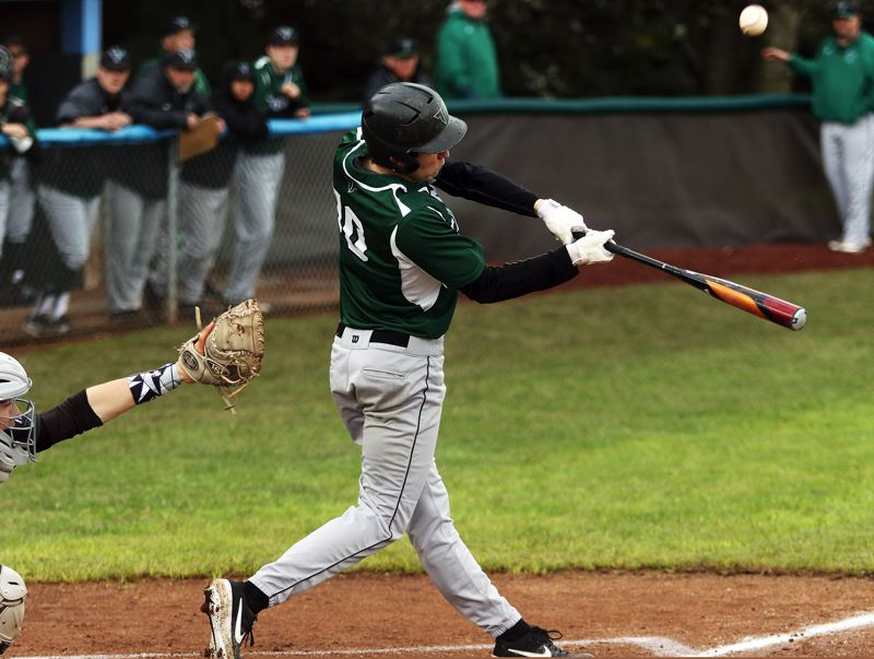 TIMES PHOTO: DAN BROOD - Tigard High School senior Nick Heinke puts the ball in play during the first inning of Tuesdays Three Rivers League game at Lakeridge.