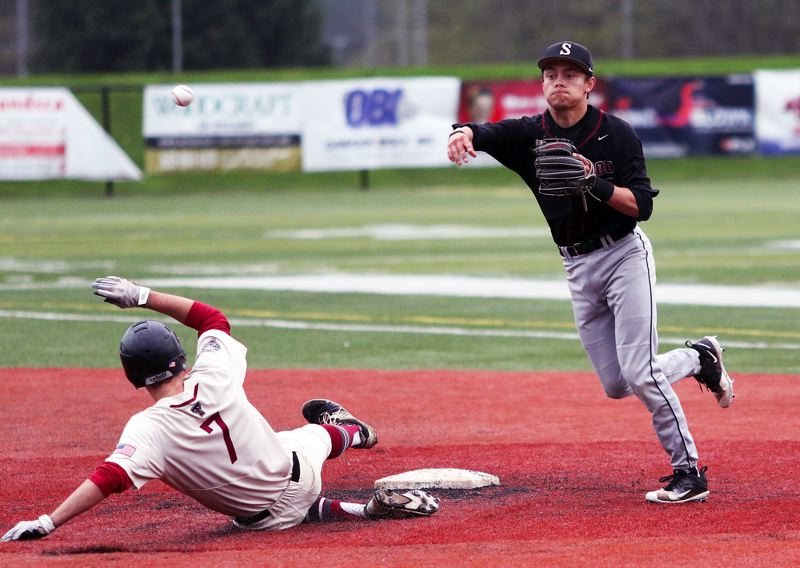TIMES PHOTO: DAN BROOD - Sherwood junior shortstop Anthony Garrett (right) makes a throw to first after forcing out Tualatins Chris Freese during Saturdays game.