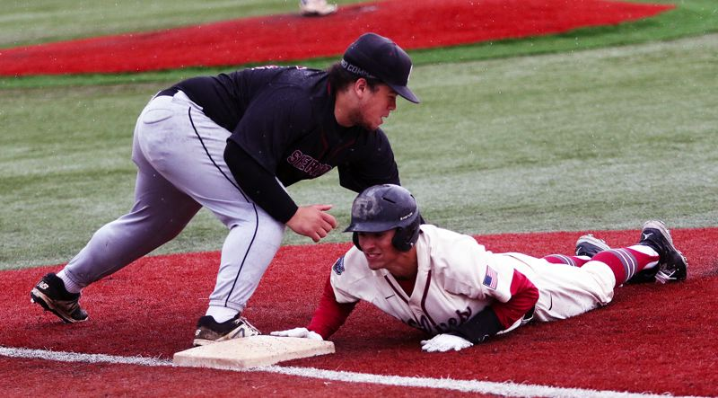 TIMES PHOTO: DAN BROOD - Tualatin senior Kaden Cook dives safely back to first base before Sherwood senior Nic Garrison can make the tag during Saturdays game.