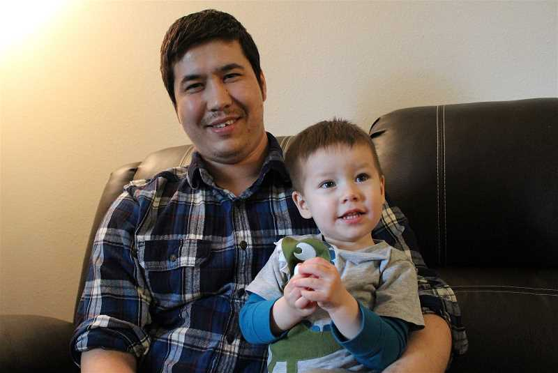 REVIEW PHOTO: SAM STITES - Mohammad Fawad Mohammadi spends time with his son, Matin, at their home in Aloha on Tuesday. The Palisades Market employee spent six weeks in the hospital after a brutal attack on the Oregon coast.