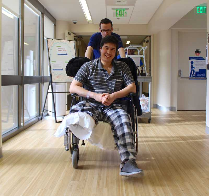 REVIEW PHOTO: SAM STITES - Mohammad Fawad Mohammadi smiled wide as he was wheeled out of the hospital last week by staff at Legacy Emanuel Medical Center.