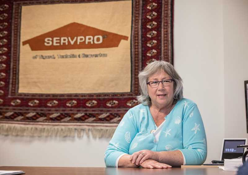 THE TIMES: JONATHAN HOUSE - Kathy Linderman sits under a handcrafted rug with the company's logo, a gift from her son who previously served in the Peace Corps in Turkmenistan.